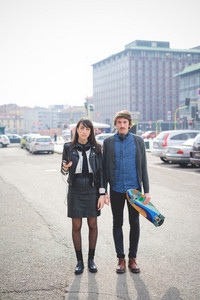 Couple of young caucasian woman and man with a skate and moustache posing trough the streets of the city listening to music by technological device - carefreeness, friendship, love, youth concept