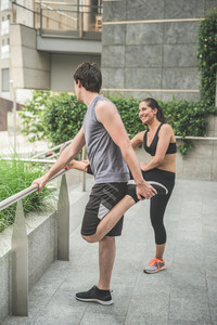 Couple of young handsome caucasian man and woman stretching, talking and laughing to each other in the street of the city - sportive, healthy, fitness concept