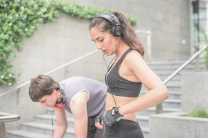 Couple of young handsome caucasian man and woman wearing headphones, preparing themselves for training - music, training, fitness concept