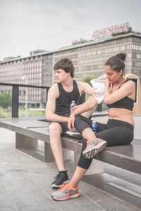 Couple of young handsome caucasian sportive man and woman having a break after training, drinking water and drying themselves with a towel - sportive, fitness, health concept