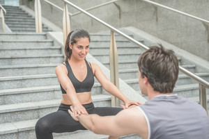 Couple of young handsome caucasian sportive man and woman helping each other to do squat, staring into each other's eyes - sportive, healthy, fitness concept