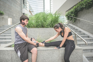Couple of young hansome caucasian sportive man and woman helping each other stretching - he helps her to stretch her leg, both looking downward - sportive, fitness, healthy concept