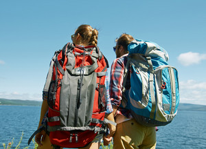 Couple of young hikers with backpacks looking at sea