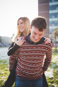 Couple of young lovers embracing outdoor in the city. She is riding piggyback, overlooking right laughing. He is looking downward, smiling - happiness, love, relationship concept