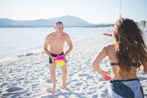 couple of young multiethnic friends women and men at the beach in summertime playing with ball