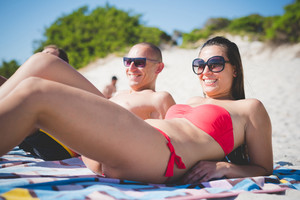 couple of young multiethnic friends women and men relaxing and having fun at the beach in summertime - relax, friendship concept - relax, friendship concept