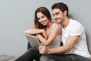 Couple sitting on the floor in studio with tablet computer. Isolated gray background