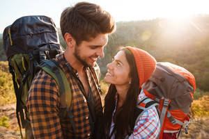 Couple with backpacks in the mountains. eyes to eyes