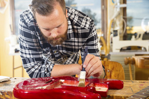 Craftsman with beard working at workshop with a guitar restoration