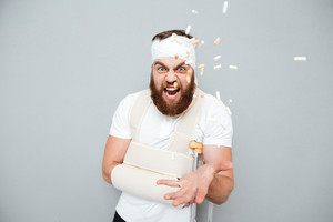 Crazy hysterical bandaged bearded man catching pills over gray background