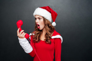 Crazy raged young female in red santa claus outfit shouting at red telephone receiver over black background