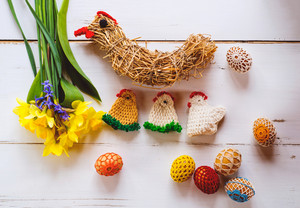 Crocheted Easter eggs, chickens, straw hen and fresh daffodil bouquet against white wooden background. Easter composition.