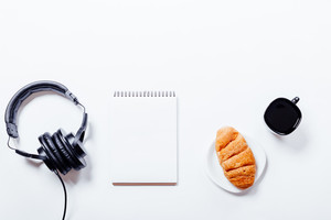 Croissant, coffee, headphones and notebook on white table, top view