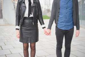 Cropped front view of young caucasian man and woman posing in the streets of the city hand in hand- carefreeness, friendship, love, youth concept
