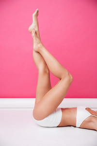 Cropped image of a beautiful young female body in white bikini with raised legs isolated on the pink background