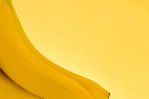 Cropped image of a bunch of bananas isolated on yellow background