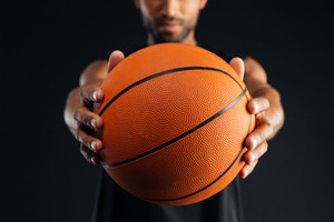Cropped image of a focused young african basketball player giving ball isolated on a black background