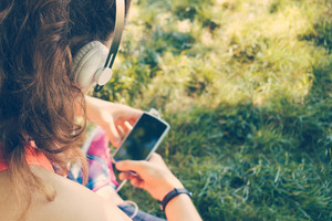 Cropped image of a girl in headphones listen to music and use a smart phone on the lawn in the summer, yellow toning