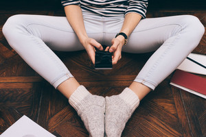 Cropped image of a girl in jeans sits at home on the floor and uses a smart phone, close-up