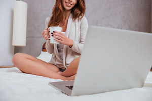 Cropped image of a happy young woman holding cup of tea and looking at laptop while sitting on bed at home