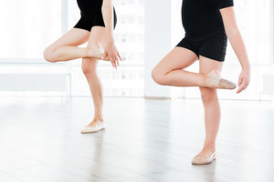 Cropped image of a little dancer and her dancing teacher in a studio