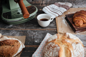 Cropped image of a lot of bread on table near cup of coffee.
