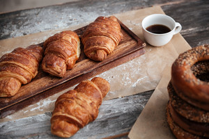 Cropped image of a lot of pastries croissants on table near cup of coffee.