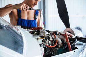 Cropped image of a repair man in overall fixing engine on a plane