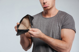 Cropped image of a sad casual man showing empty wallet over white background