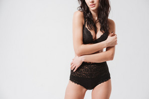 Cropped image of a sexy brunette woman in black lingerie standing with hands crossed isolated on a white background