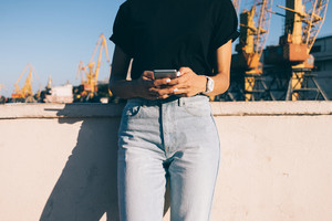 Cropped image of a slender girl in jeans with a phone on the background of a seaport in summer