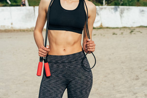 Cropped image of a slim woman in sportswear with a skipping rope in her hands on the beach in the morning