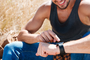 Cropped image of a smiling man using smart watch while sitting outdoors