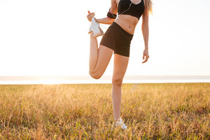 Cropped image of a sports woman doing legs stretching exercises outdoors
