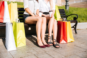 Cropped image of a two women resting on a bench together with shopping bags