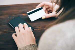 Cropped image of a woman enters information from a credit card into her smart phone, view from the back