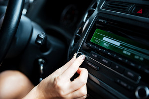 Cropped image of a woman hand turning button of radio in car