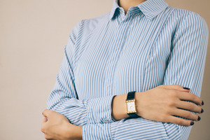 Cropped image of a woman in a business shirt and watch, close-up
