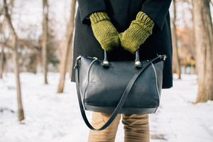 Cropped image of a woman in a coat holding her purse in hands outdoors in winter