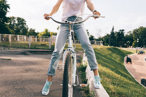 Cropped image of a woman in jeans and a T-shirt sitting on a city bicycle in a park, close-up