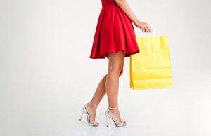 Cropped image of a woman in red dress and sandals holding yellow shopping bag isolated on a white background