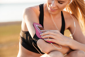 Cropped image of a woman runner listening to music with mobile phone in armband outdoors