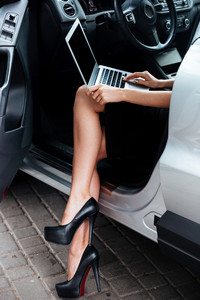 Cropped image of a young businesswoman working on her laptop computer while sitting in car