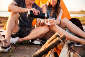 Cropped image of a young couple drinking tea at the bonfire while camping