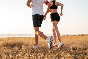 Cropped image of a young fitness man and woman doing jogging sport outdoors