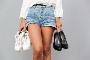 Cropped image of a young girl in denim shorts holding two pairs of shoes over gray background