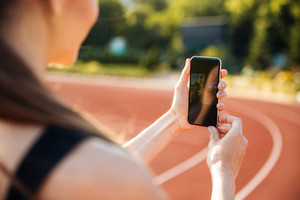 Cropped image of a young sportswoman making selfie photo on mobile phone after training outdoors