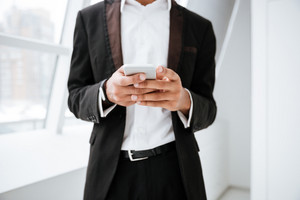 Cropped image of african business man writing message on phone and standing near the window in office
