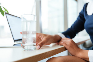 Cropped image of afro Business woman in dress sitting by the table with cup of water and pill in office. Focus on cup
