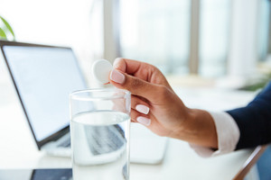Cropped image of afro Business woman in dress with water and pill by the table in office